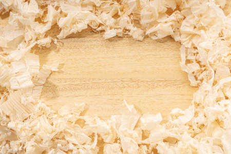 Carpentry or woodworking background with copy space. Border frame of wood shavings on wood table. Woodworking, craftsmanship and handwork concept, flat lay. Stock fotó