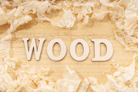 Wooden word or wood table ans wood shavings. Woodworking, craftsmanship and handwork concept, flat lay