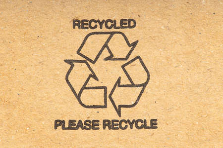 Recycle symbol on brown recycled cardboard background. Close up Stock fotó