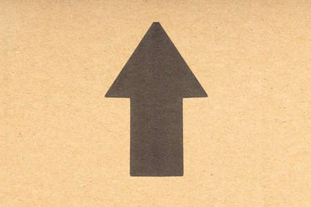 Black arrow pointing up on brown cardboard background. Close up