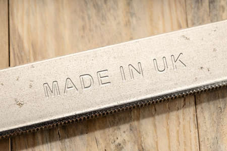 Made in UK engraved on steel tool on wooden table. Close up