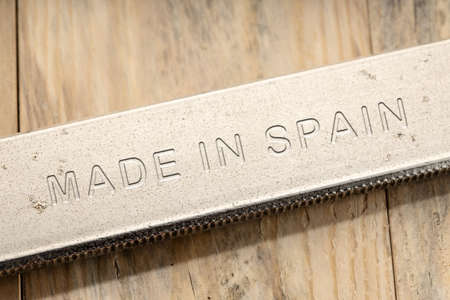 Made in Spain engraved on steel tool on wooden table. Close up