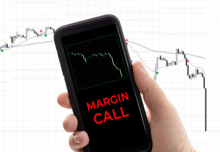Hand holding a smartphone with the message margin call. Trading loss stock exchange. Brokerage account