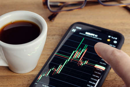 Stock market trading on portable device concept. Finger touching a Chart on smart phone screen on desk
