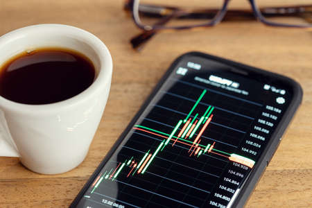Stock market trading on portable device concept. Chart on smart phone screen on desk. Trading or investment concept Stock fotó