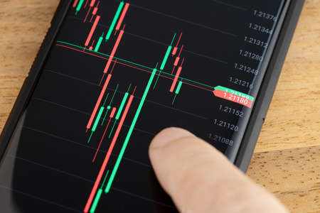Finger on Stock market Chart on smart phone screen. Trading on portable device concept Stock fotó