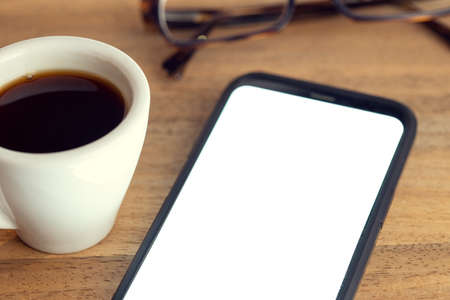 Smart phone on desk with white screen, eyeglasses and cup of coffee on wooden table. Mock up template