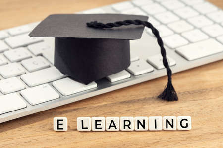 E-Learning or home study concept. Graduation cap on computer keyboard on wooden desk Stock fotó