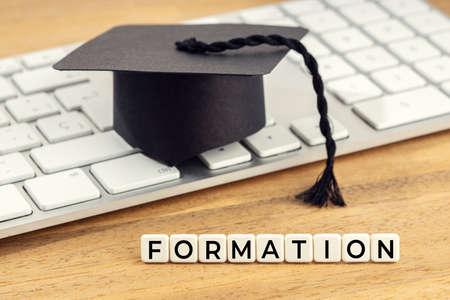 Formation concept. Graduation cap on computer keyboard on wooden desk