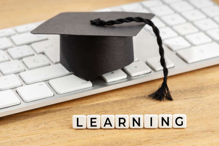 Learning concept. Graduation cap on computer keyboard on wooden desk