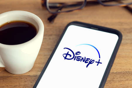 Galicia, Spain; february 15, 2021: Disney plus logo on Smart phone screen on desk with eyeglasses and cup of coffee on wooden table Sajtókép