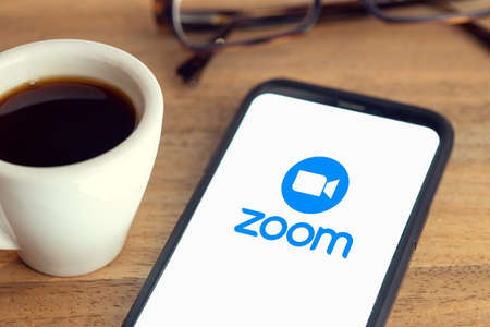 Galicia, Spain; february 15, 2021: Zoom logo on Smart phone screen on desk with eyeglasses and cup of coffee on wooden table