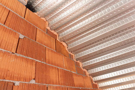 Roof detail with Metal decking sheet and brick wall on construction site. Composite decking for roofing. Construction industry