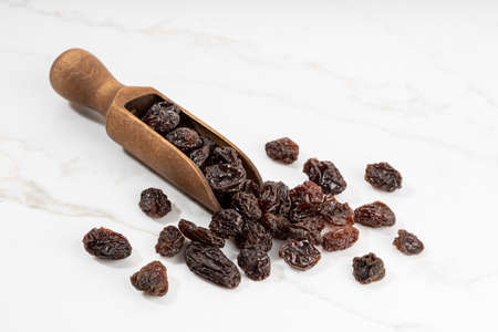 Raisins and scoop isolated on White marble Background. Dried grape. Copy space