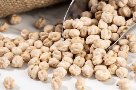 Close up of Chickpeas on scoop on White marble Background. Cicer arietinum