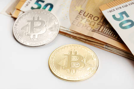 Bitcoin coins and Euro banknotes. Cryptocurrency versus fiat money concept Reklamní fotografie