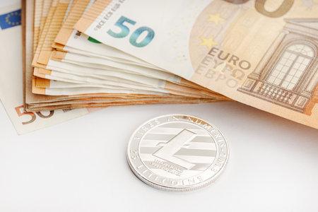 Litecoin coin and Euro banknotes. Blockchain money versus fiat money concept 版權商用圖片