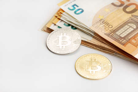 Bitcoin coins and Euro banknotes. Cryptocurrency versus fiat money concept