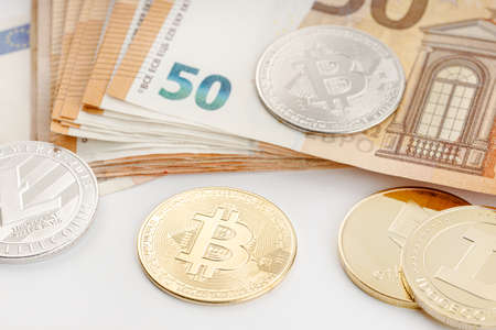 Group of Cryptocurrency coins and Euro banknotes. Blockchain money versus fiat money concept