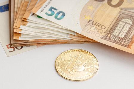 Bitcoin coin and Euro banknotes. Blockchain money versus fiat money concept