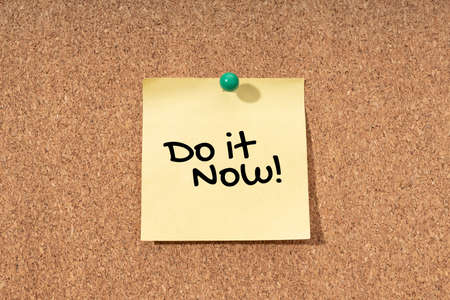 Do it now message on yellow note on cork board
