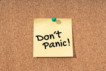 Dont panic message on yellow note on cork board