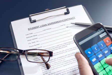 Blank Student Loan Application on table and hand holding a smartphone with calculator app. Education cost