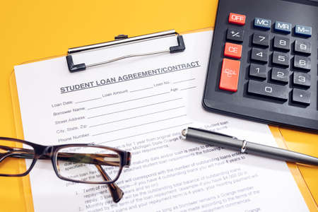 Blank Student Loan Application, calculator, pen and eyeglasses on table. Education cost concept 版權商用圖片