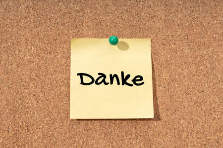 Thanks word in german language on yellow note on cork board