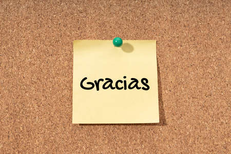 Thanks word in spanish language on yellow note in cork board