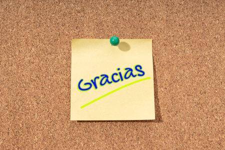 Thanks word in spanish language on yellow note on cork board 版權商用圖片