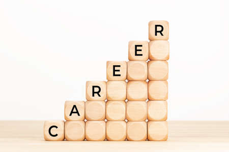 Career Growing concept. Text in wooden dices on table. White background. Copy space