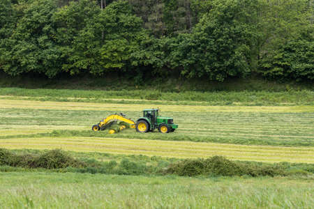 Beautiful rural scene of a tractor and machinery harvesting cut grass in an agricultural field. Pastures for animal food