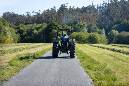 Scene of a old tractor seen from behind on a road in a rural area. Galicia, Spain Stock Photo