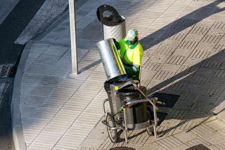 Street sweeper unloading a garbage can on pushing a cart on sidewalk. Urban cleaning concept
