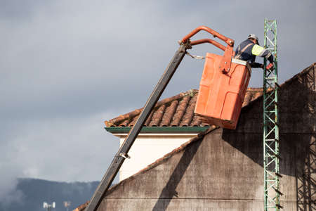 Worker on telescopic elevator working with a angle grinder on a roof of a building 版權商用圖片