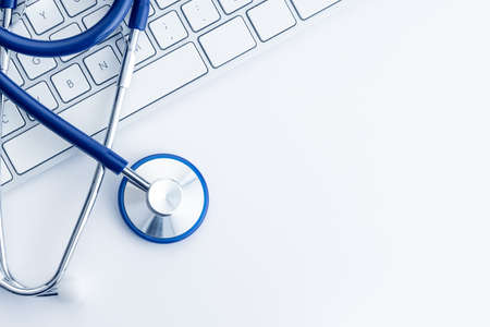 Stethoscope on computer keyboard on white desk. Online health care or telemedicine concept. Medical background. Top view. Copy space