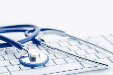 Close up of a Stethoscope on computer keyboard on white desk. Online health care or telemedicine concept. Medical background. Copy space