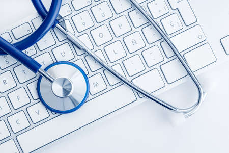 Stethoscope on computer keyboard on white desk. Online health care or telemedicine concept. Medical background. Top view