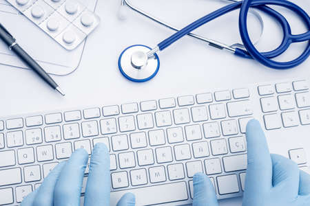 Doctor Hands in gloves typing on computer keyboard on white desk. Telemedicine or medical technology concept background. Top view