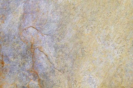 Natural stone background texture with yellow, beige and purple tones