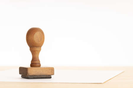 Vintage Rubber stamp and blank paper on wooden table. White background. Copy space 版權商用圖片