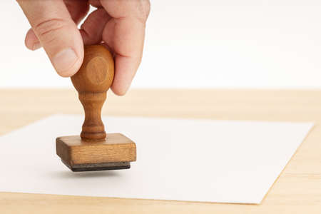 Hand holding a Rubber stamp and blank paper on wooden table. White background. Copy space