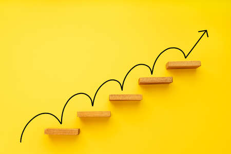 Rising arrow on staircase on yellow background. Growth, increasing business, success process concept. Copy space 版權商用圖片
