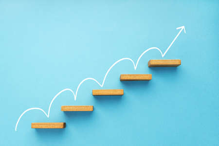 Rising arrow on staircase on blue background. Growth, increasing business, success process concept. Copy space