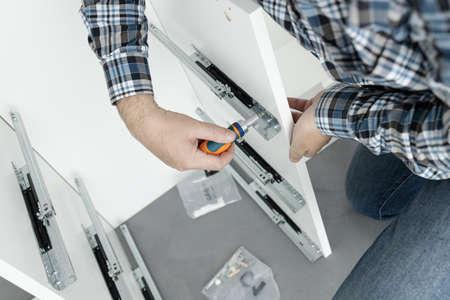 Man Assembling a drawer slider Furniture using a screwdriver 版權商用圖片