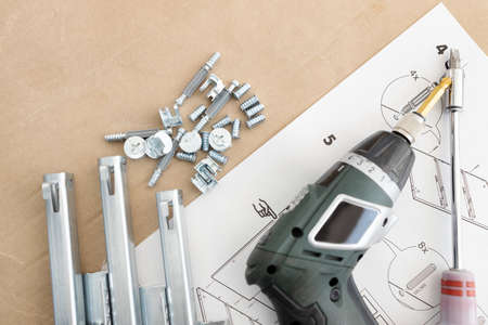 Top view of a cordless screwdriver, drawer sliders, screws and accessories. Assembling furniture concept. Copy space