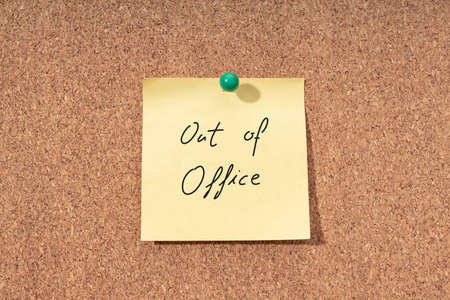 Yellow note with phrase out of office on cork board