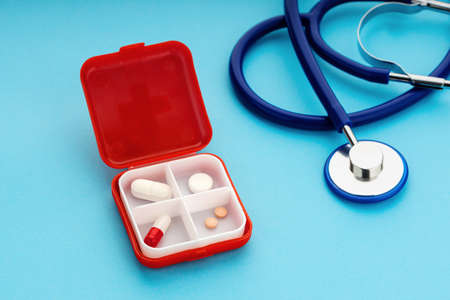 Daily Pill box and stethoscope on blue background. Medicine, healthcare and pharmacy concept