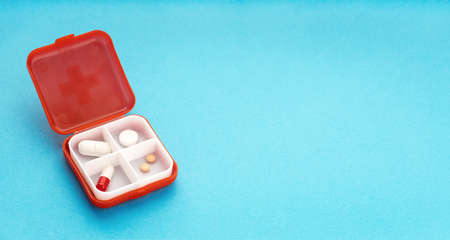 Daily Pill box isolated on blue background. Medicine, healthcare and pharmacy concept. Copy space